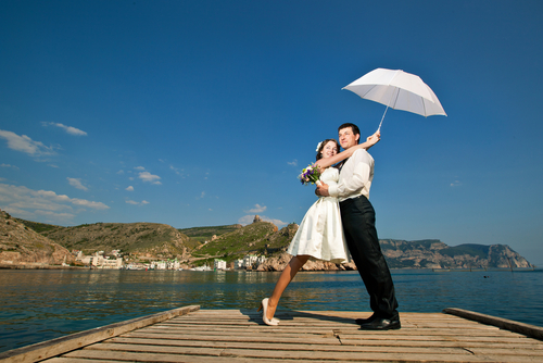 Bride and Groom with Parasol on Dock