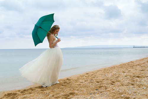 Bride on beach with Parasol